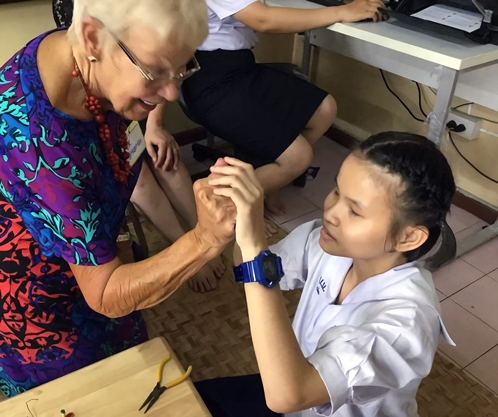 Barbara communicating with  a girl  arround 7 years old.  They are using tactile sign language.