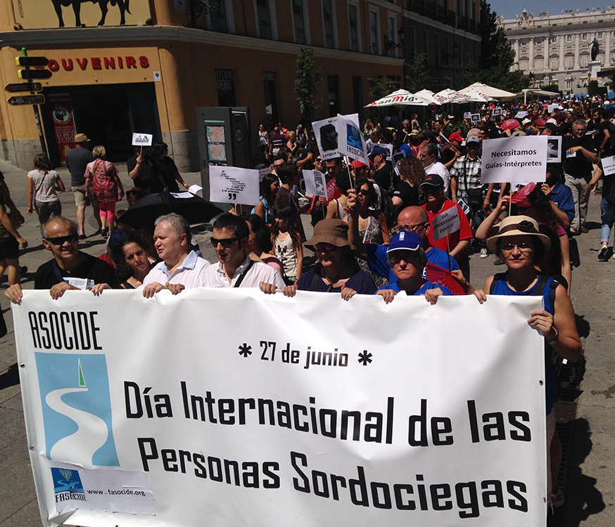 Group of people marching on a narrow street  with 6 people  holding a big sign that reads: June 27th. International Day for people with deafblindness