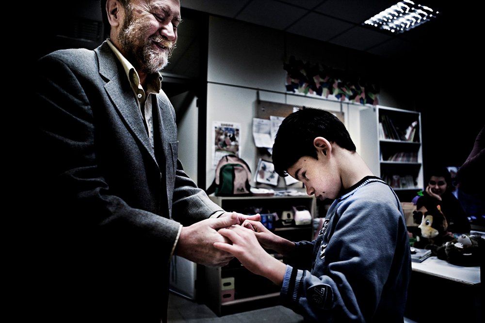 Daniel  communicating through tactile sign language with a young  boy.  Both are  smiling.